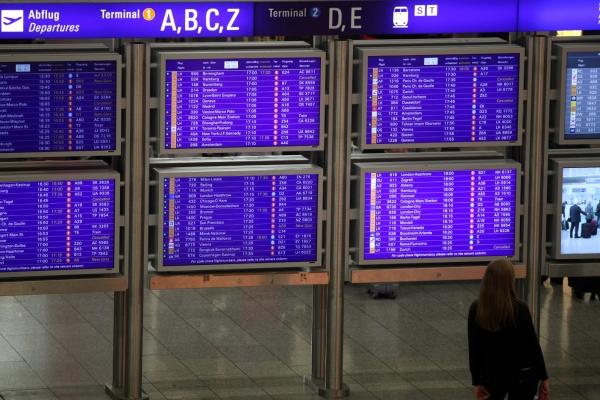 Frau vor Informationstafel am Frankfurter Flughafen, über dts Nachrichtenagentur