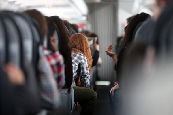 Rothaarige Frau in einem Flugzeug, über dts Nachrichtenagentur